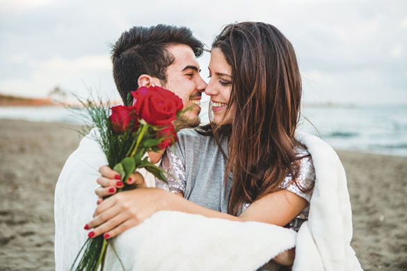 loving-couple-sitting-beach-with-bouquet-roses
